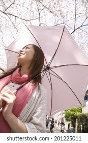 Woman walking around with a sun shade under the cherry tree
