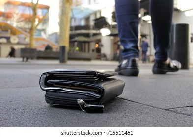 Woman walking away after losing her wallet on city street. loss concept. Real people. Copy space