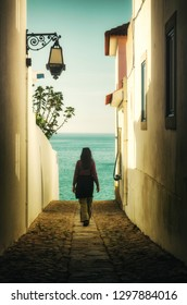 Woman walking away in an alley between houses into the sea