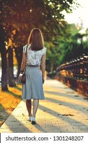 Woman walking away. Back view full length portrait