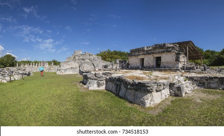 woman walking away in the distance while walking in the ruins of the archaeological zone The King in front of the Beach Delfines, Quintana Roo