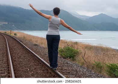 woman walking balanced on the train tracks