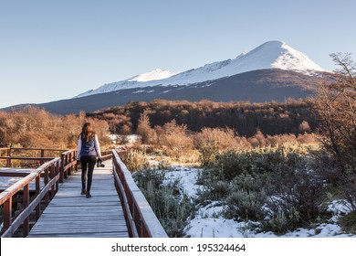 Woman walking in a balcony with a beautiful landscape in the background. Ushuaia, Argentina