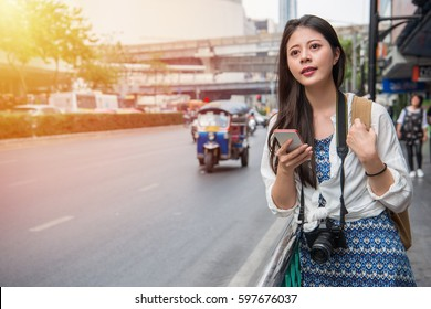 Woman walking in bangkok city using phone app for taxi ride hailing service or using phone app to find directions and guide during travel. Asian girl tourist on street near tuk tuk car.