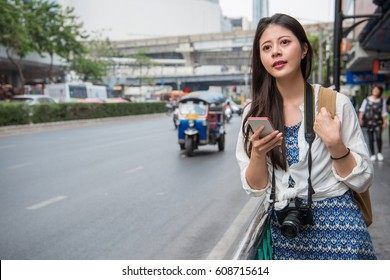 Woman walking in bangkok city using phone app for taxi ride hailing service or reading travel guide. Asian girl tourist searching for map directions on smartphone. Copy space.