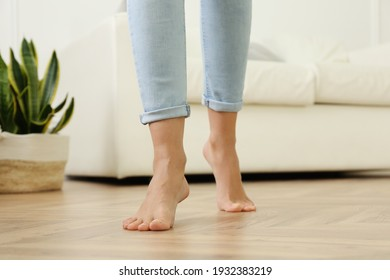 Woman walking barefoot at home, closeup. Floor heating concept