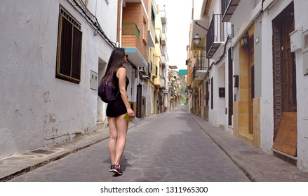 Woman walking from behind with backpack.She is walking on a tight old street.Travel concept.