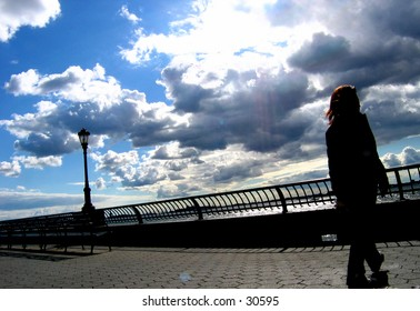 Woman walking by Battery Park. Developing Thunder Clouds