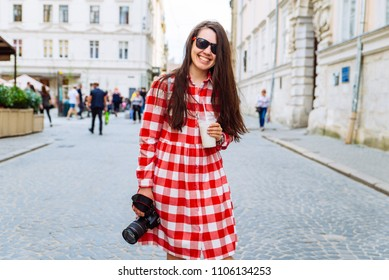 woman walking by city streets with cool drink and camera