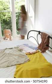 Woman walking by outfit laid out on bed