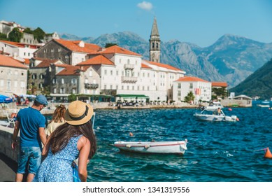 woman walking by Perast city. summer vacation. sea bay. mountains on background