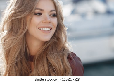 woman walking by sea. spring portrait. smiling girl in autumn city