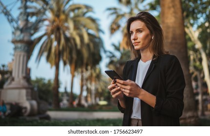 Woman walking and chatting with office manager outside in city park barcelona, successful businesswoman typing on touch screen of cellphone while internet technology outdoors