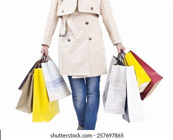 woman walking with colorful shopping bags in hands, isolated on white.