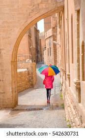 Woman walking with colorful umbrella Old Mardin street Mardin/Turkey