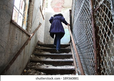 woman walking up dangerous steps in an abandon mental institution
