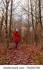 Woman walking down autumnal woodland path alone, dressed in warm clothes and hat, with knee-high boots. At one with nature, she reaches up to touch bare tree branches.