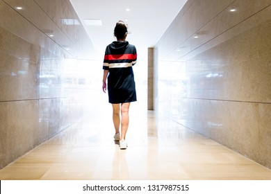 Woman walking down a corridor towards lit exit