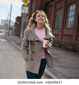 Woman walking down and drinking coffee