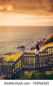 Woman walking down Hallett Cove boardwalk to enjoy sunset from beach, South Australia