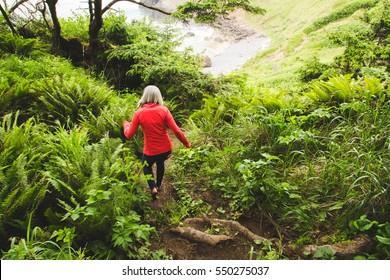 Woman walking down lush hiking trail in Oregon. Cannon Beach, Oregon, USA.