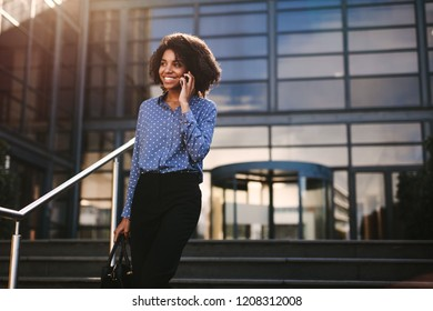 Woman walking down the steps outside office building and talking on mobile phone. Businesswoman talking on cell phone with office building in background.