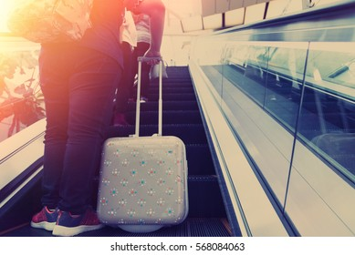 Woman walking up the escalator in the modern airport,traveler and tourist concept.