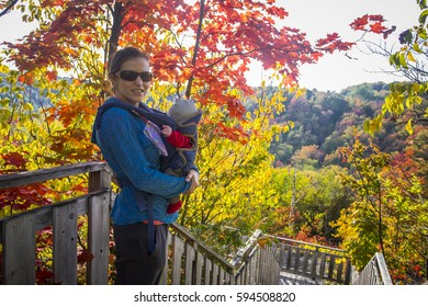 woman walking in a fall forest with baby in chest carrier