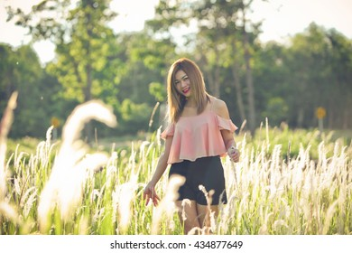 Woman walking in a field of grass. , Portrait Photography woman Thailand
