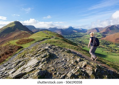 A woman walking the footpath up to Cat Bells, a peak in the Derwent Fells near Keswick in the English Lake District.