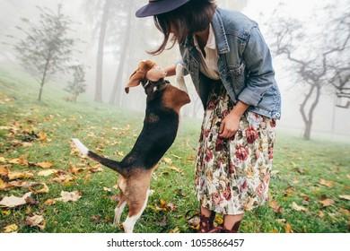 woman walking her beagle dog in town