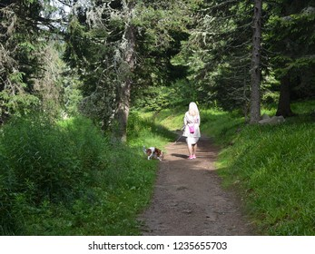 Woman walking with her dog on a path through a forest