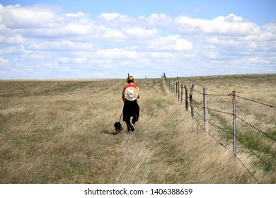 A woman walking her dog in the prairie grass of South Dakota along a fence line.  She has her hat hanging on her back and is walking away from the camera.