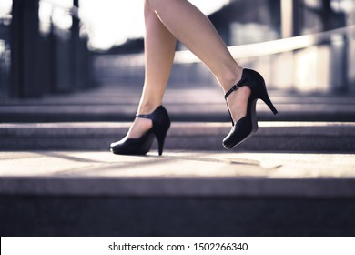 Woman walking in high heels in urban city street in summer. Chic stylish footwear. Elegant fashion style. Business lady with sexy stiletto shoes. Confident and powerful female boss. Luxury lifestyle.