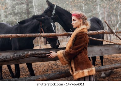Woman walking with horse autumn on nature. Creative hot pink makeup girl face, hair coloring. Portrait of a girl with a horse. Horse riding in the autumn forest. Autumn clothes and bright red makeup