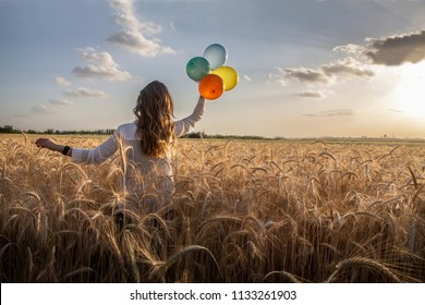 a woman walking int the wheat field holding four color baloon