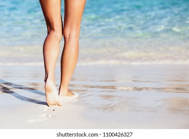 Woman walking into the sea, body part, perfect tanning women's legs, enjoying time on the beach, summer vacation concept