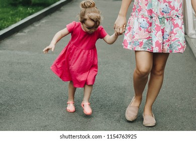 Woman walking with little girl in the street