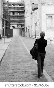 A woman walking a narrow straight street of a medieval italian town. lack and white photo, focus on the model.