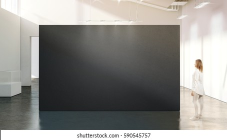 Woman walking near blank black wall mockup in modern white gallery. Girl admires a dark big stand mock up in museum with contemporary art exhibitions. Large hall interior, grey banner exposition