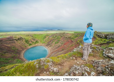 Woman walking near crater of a old active volcano Kerith filled with water. Iceland.