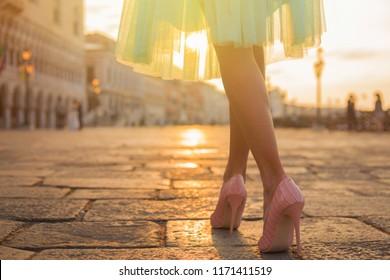 Woman walking in old city by sunrise