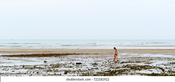A woman is walking on the beach.