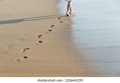 Woman walking on beach leaving footprints in the sand.