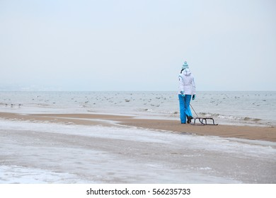 A woman walking on the beach with a sledge