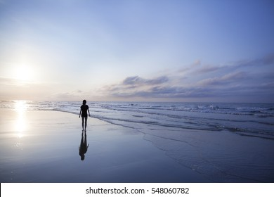 Woman walking on beach at sunrise