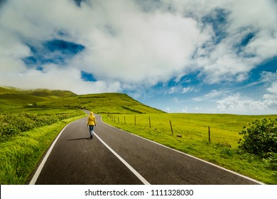 Woman walking on a beautiful road on Flores Island, Azores, Portugal