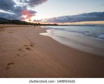 Woman walking on big beach, just outside of Kihei, Maui, Hawaii.