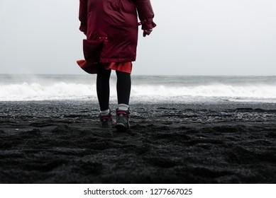 Woman walking on the Black sand Reynisfjara Beach in Iceland back view