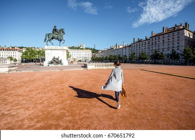 Woman walking on the famous Bellecour square with Louis king statue traveling in Lyon city in France